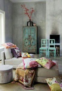 Kékre festett szekrény és székek, színes párnák egy kanapén