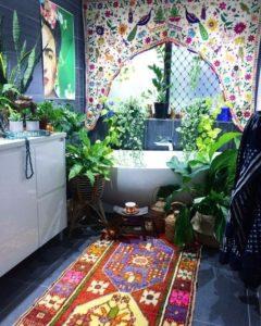 Fürdőszoba káddal, színes függönnyel, mintás szőnyeggel és növényekkel