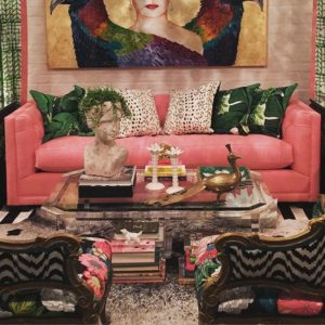 Rózsaszín fotelen zöld párnák, egy asztal és színes festmény