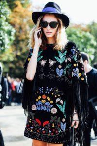 Hímzett fekete ruhában egy nő telefonál