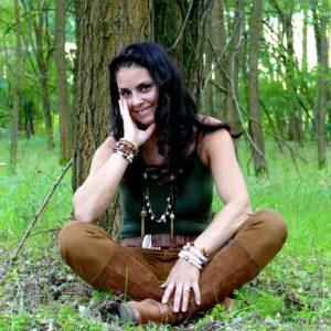 egy lány ül törökülésben az erdőben