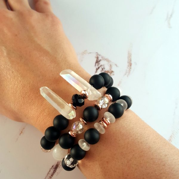 három darab fekete-fehér karkötő egy nöi kézen