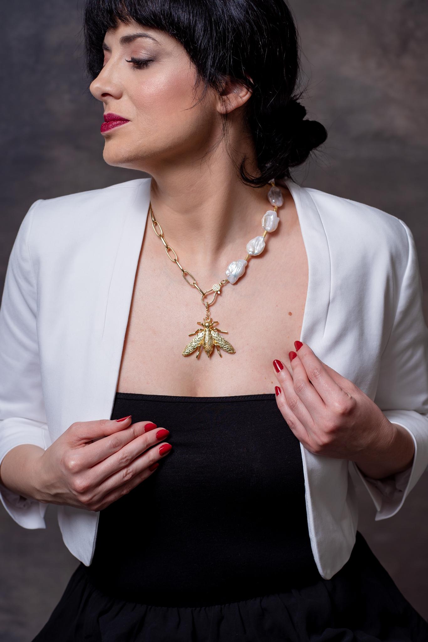 méhecske medálos édesvízi gyöngyös nyaklánc egy női modellen
