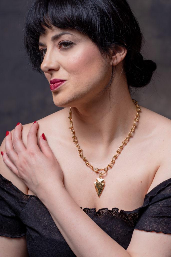 nyílhegy medálos aranyozott nyaklánc egy női modellen