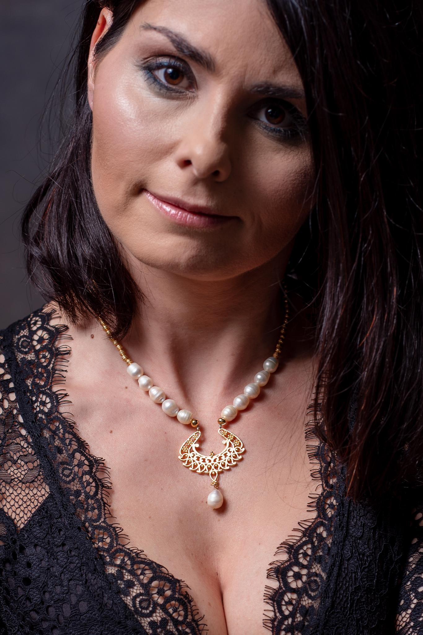 édesvízi gyöngyös nyaklánc aranyozott medállal egy női modellen